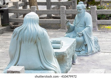 Laoshan,China 21/04/2016 Two stone sculptures discussing and sitting at a table, one is Confucius and one is Lao Tse, the spiritual leader of Daoism outside in a temple park in Laoshan, China