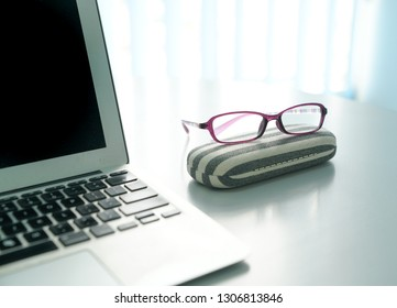 Lap top and spectacles on office desk with windows at the background