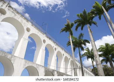 Lapa Arches Rio de Janeiro Brazil under bright tropical blue sky with palm trees