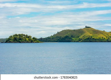 Lapinig Island and Bonoon islet of the town of President Carlos P. Garcia, Bohol. Small rolling hills covered by grasses jut out from the blue glassy ocean.