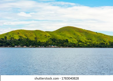 Lapinig Island, the main island of the town of President Carlos P. Garcia, Bohol. Small rolling hills covered by grasses jut out from the blue glassy ocean.