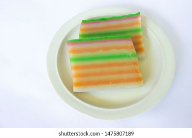lapis cake or roti lapis or layer cake or lapis legit served in little plate isolated on white background made from rice flour, starch, coconut milk, sugar, salt and coloring