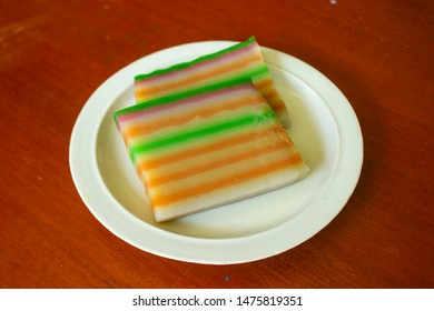 lapis cake or roti lapis or layer cake or lapis legit served in little plate on wood background made from rice flour, starch, coconut milk, sugar, salt and coloring