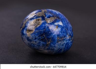 Lapis Lazuli geode on black background. Beautiful natural crystal gemstone.