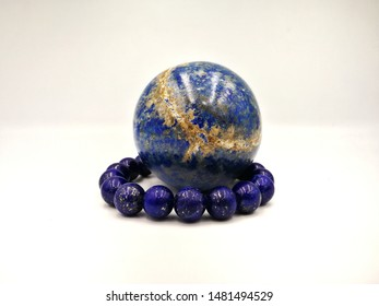 Lapis lazuli stone for meditation in globe or ball shape and lapis lazuli bracelet isolated on white background