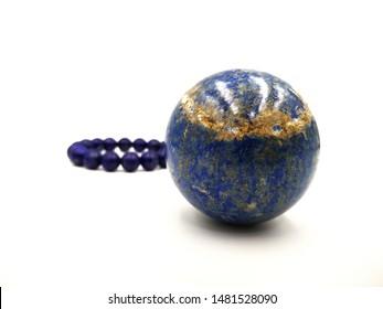 Lapis lazuli stone for meditation in globe or ball shape and lapis lazuli bracelet isolated on white background ,focus on ball stone