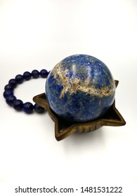 Lapis lazuli stone for meditation in globe or ball shape on antique brass bowl and lapis lazuli bracelet isolated on white background,focus on ball shape stone