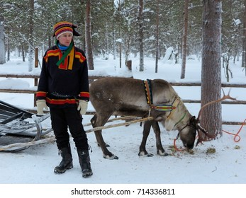 LAPLAND, FINLAND - FEBRUARY 2, 2017: A Sami man in traditional clothing stands beside a reindeer and sleigh in Finnish Lapland.