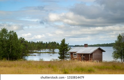 Lapland summer landscape. Beautiful small wooden house on the lake shore, Finland.