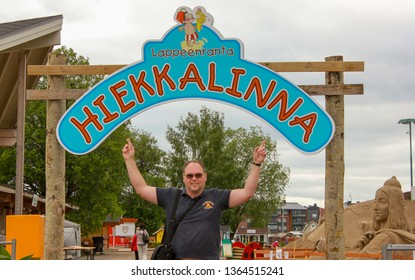 Lappeenranta, Finland. 12.06.2012. The man raised his hands in a dark Polo against the entrance to the sand sculpture Park