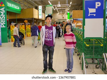 Lappeenranta, Finland. 12.06.2012. A young man and a girl standing next to the shopping carts in the supermarket
