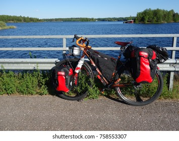 LAPPEENRANTA, FINLAND - JUNE 29, 2015: touring bike and red panniers and other touring and camping gear attached to the bike by a lake Saimaa near Lappeenranta in Eastern Finland.