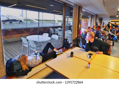 LAPPEENRANTA, FINLAND- OCTOBER 10, 2018: Tourists are waiting in crowded departures room near the gates for the delayed Ryanair flight in airport, watching preparation of a plane for low cost airline.