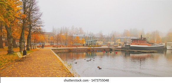 Lappeenranta port with boat at autumn day. Sights of Lappeenranta harbor and garden, beautiful fall tree yellow leaves amazing view. October autumn park foliage and lake fog scene, travel in Finland