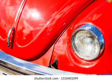 Lappeenranta/Finland - May 2 2017: Red bright bonnet of vintage and retro car. Fragment, part of old cute car in a daylight on a bright sun light and sunshine. One headlight and red bonnet of a car.