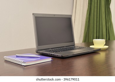 Laptop an address book and pen on the brown table.