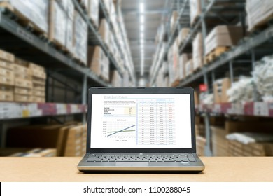 Laptop with analysis sale screen on table with blur warehouse cargo in factory. Smart factory concept.