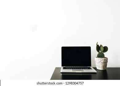Laptop with blank mock up screen and succulent on black table. Home office desk workspace minimal concept.