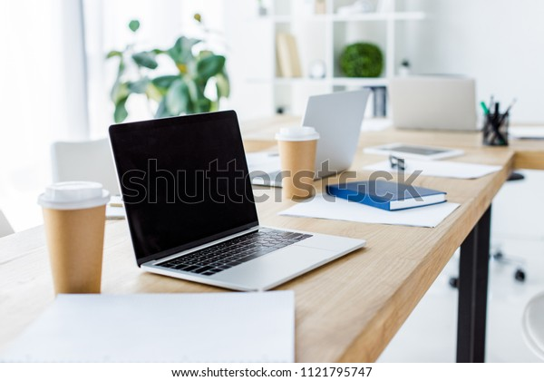 laptop with blank screen and disposable coffee cups on table in business office