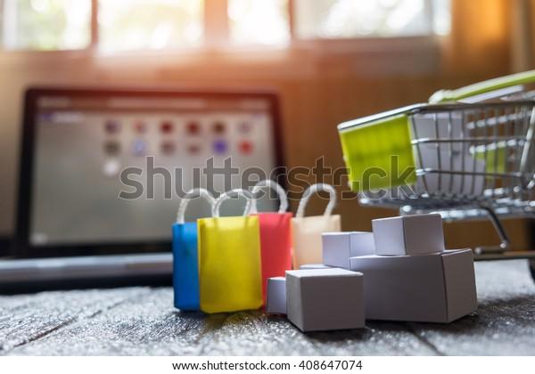 notebook prázdná obrazovka a skákání košík plný dárků s copyspace, online nakupování koncept.