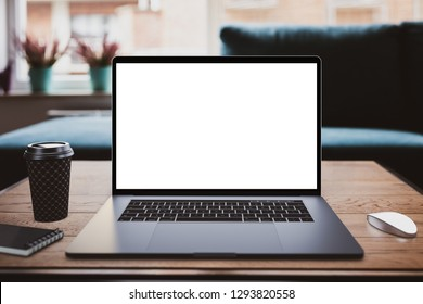Laptop with blank screen mockup on table in living room - front view