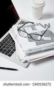 laptop with blank screen near business newspapers,glasses, pen and paper cup on white