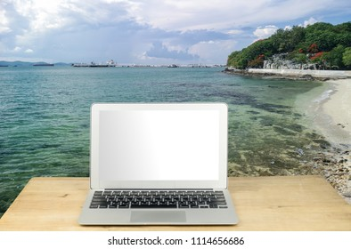 Laptop with blank screen on table by the sea
