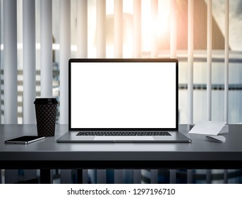Laptop with blank screen on table in skyscraper office interior building - mockup, template
