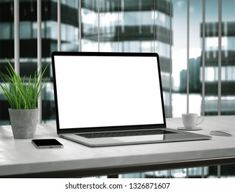 Laptop blank screen on table in office interior skyscraper building - mockup, template