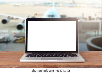 Laptop with blank screen on table work in airport, clipping path inside