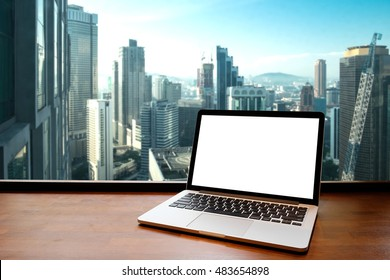 Laptop with blank screen on table in business office.