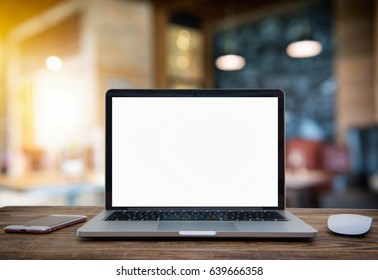 Laptop with blank screen on table of coffee shop blur background with bokeh.