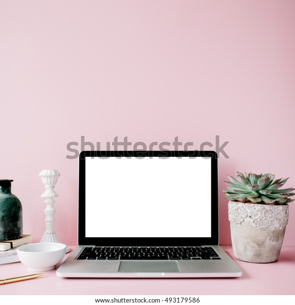 Laptop with blank screen on table with proteus flower and decoration