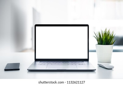 Laptop with blank screen on white table with mouse and smartphone. Home interior or office background