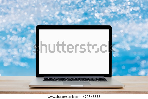 Laptop with blank screen on wood table and bokeh in pool background. Clipping path include.