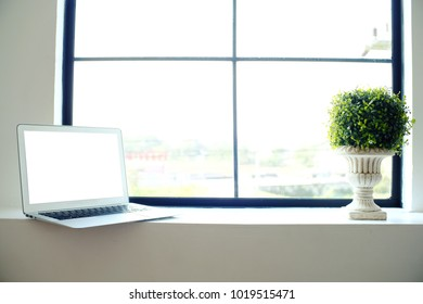 Laptop with blank screen on wooden table in front of window