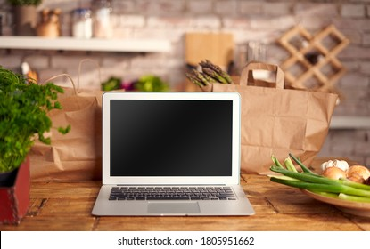 Laptop with blank screen on wooden table in the kitchen, surrounded by paper shopping bags. Concepts of online grocery store webshop and online shopping.