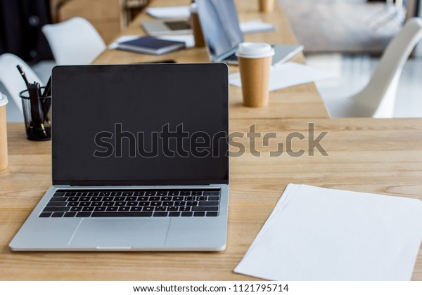 laptop with blank screen on wooden table in business office
