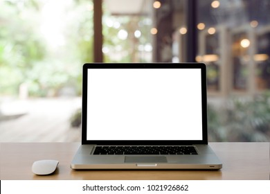 Laptop with blank screen and wireless mouse on Empty space Wooden Desk at home interior blurred background at light bokeh.