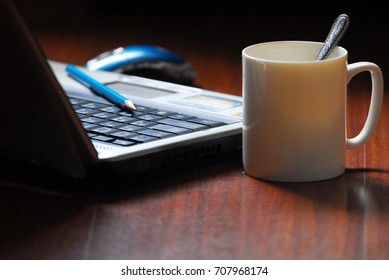 Laptop blue Mouse com pencil and white water glass on Wooden floor dark background