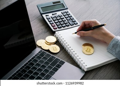 Laptop with calculator and golden bitcoin. Cryptocurrency investors concept.
