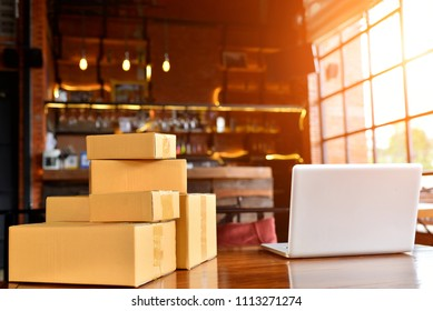 Laptop, carton box, parcel of goods to deliver to customers. Online sales of ecommerce packaging ideas