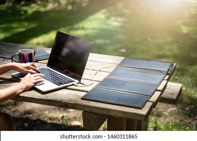 Laptop charged by solar panel outdoor on wooden table