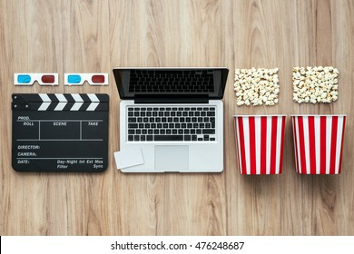Laptop, clapper board, popcorn and 3D glasses: cinema streaming and movie series online concept