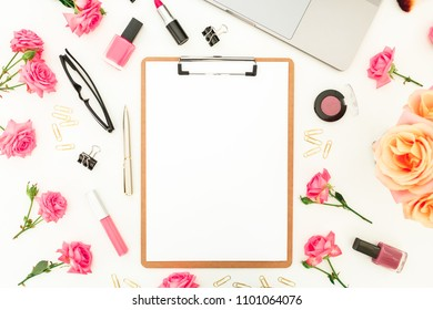 Laptop, clipboard, roses flowers, cosmetics and accessories on white background. Flat lay. Top view. Feminine office or blogger concept