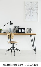 Laptop with clock on screensaver placed on hairpin desk standing under a poster hanging on white wall