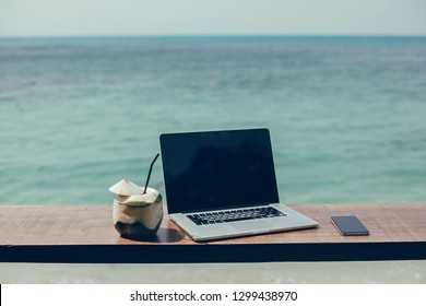 Laptop, coconut and smartphone in table. Ocean cafe