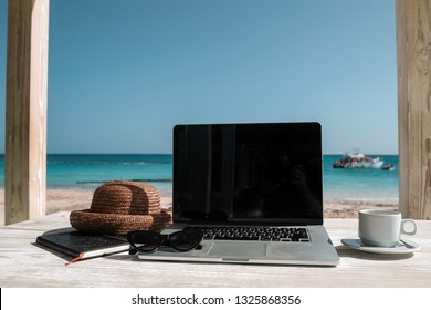 A laptop cofee cup and straw hat on wooden table and ocean view