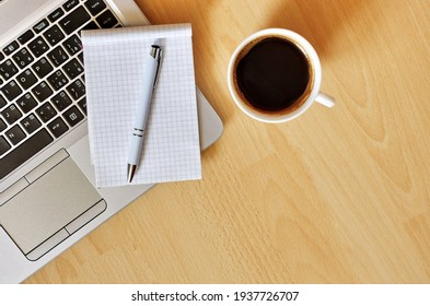 Laptop with coffee cup, notebook and pen on wooden background, concept for home office. Business concept. Work from home. desk office with laptop, blank notepad, coffee cup and pen on wooden table.