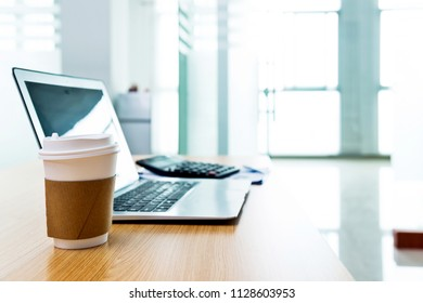 Laptop with coffee cup in office.